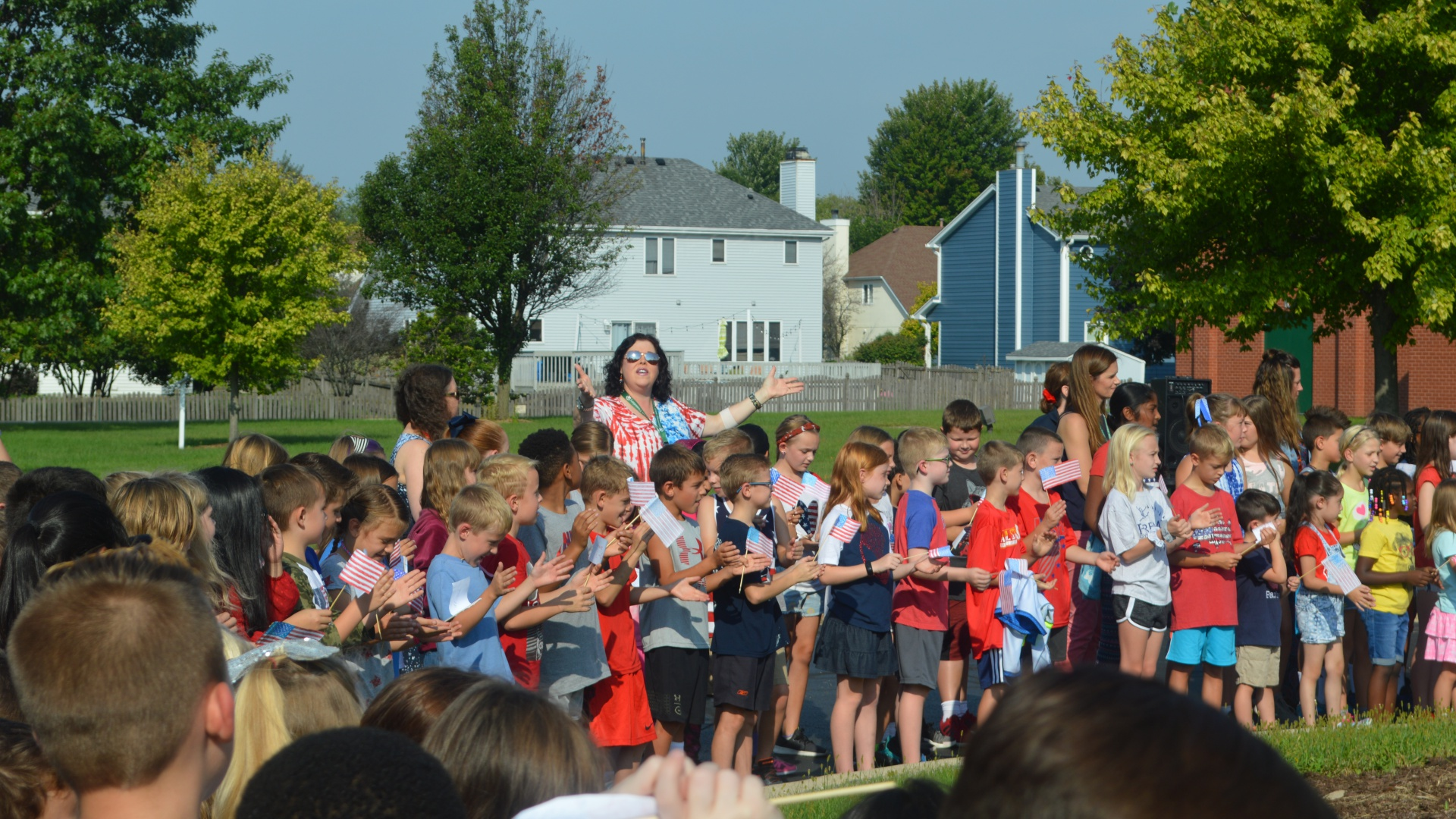 Mrs. Goolsby leading the students in song for Patriot's Day